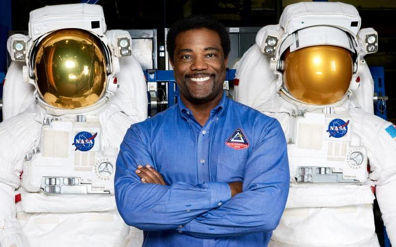 Ron Cobbs poses with space suits