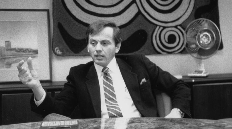 Dr. Harold Raveche sitting at a desk